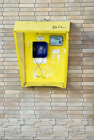 Yellow telephone box on biege brick wall Stock Photo - 2183141