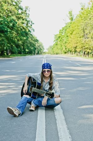 ギターと高速道路の道路上で女の子をロッキング
