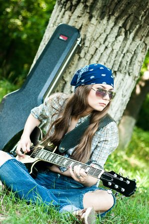 Rocking girl on a nature with guitar photo