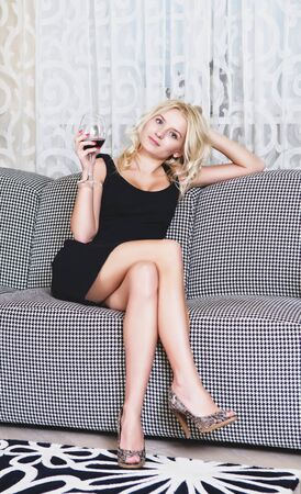 Beautiful woman with goblet of wine sitting on sofa photo