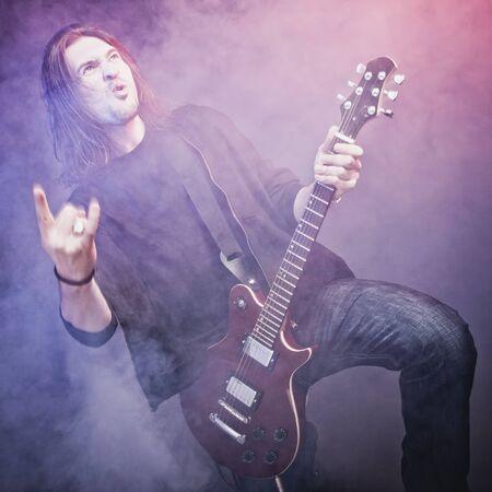 赤のエレク トリック ギターでロック スター perfoming 騒々しい音楽
