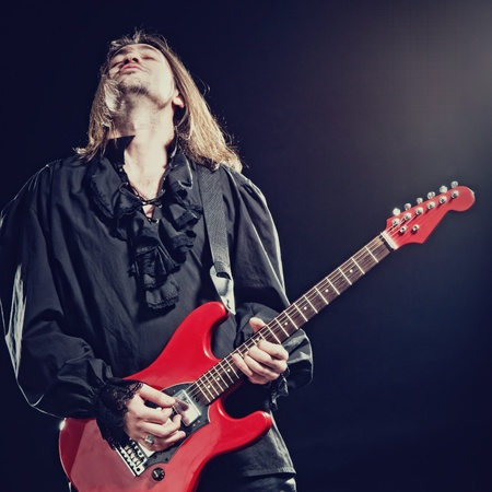 Rock-star perfoming loud music on red electric guitar photo