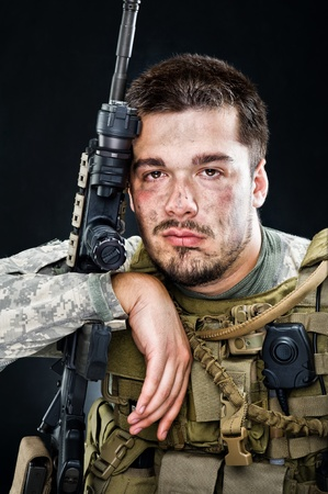 Soldier of USA army posing with a gun on a black background photo