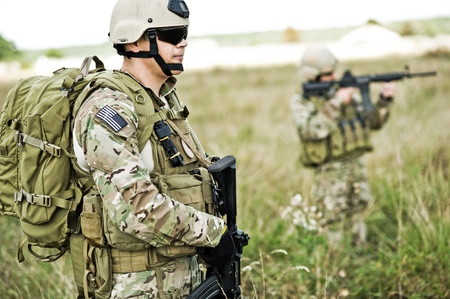 armed forces: Soldiers  in full gear patrol the area in the desert Stock Photo