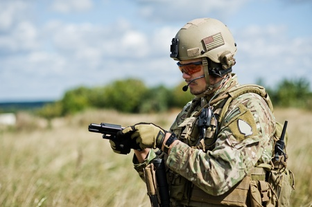 The soldier  in full gear reloads a gun photo