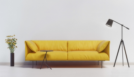 Yellow couch against a white wall with a lamp and flowers photo