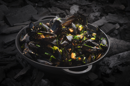 coal fish: Steamed Mussels with vegetables in a black frying pan on the coals