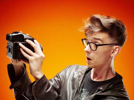 headshoot: Emotional portrait of a teenager  with film camera on a red background