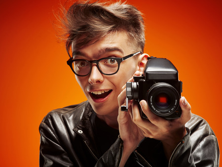 Emotional portrait of a teenager  with film camera on a red background