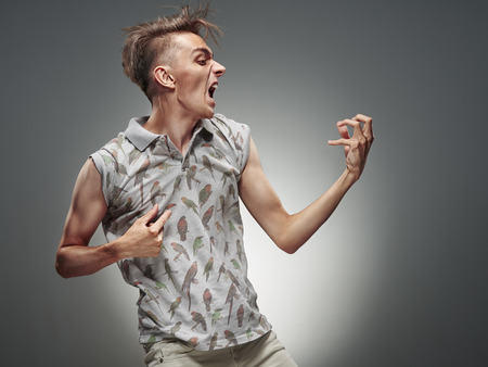 Emotional portrait of a teenager  playing on air guitar on a gray background Stock Photo