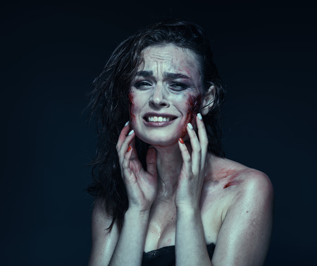 Beautiful girl with a scar on her face in the blood on a dark background Banco de Imagens