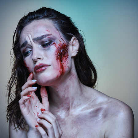 Beautiful girl with a scared wounded face in the blood on a color background