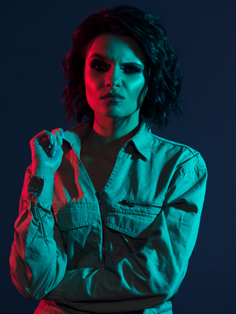 Model with reckless and haughty face expression, sarcasm and arrogance. Girl with arched eyebrow in red and blue light, curly hair and smoky eyes, khaki dress and evening makeup
