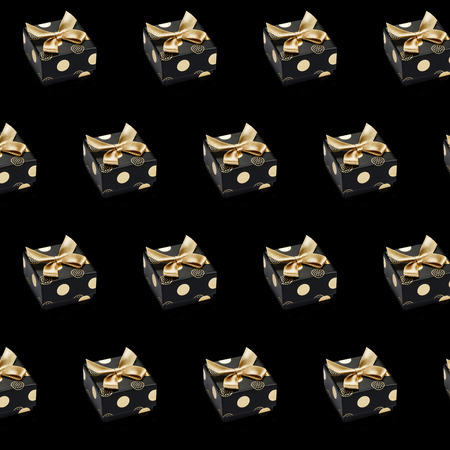 Realistic black gift boxes pattern with gold circles and bows on black background. Design for wrapping paper, greeting, invitation card, giveaways, placeholder, cover, website. 写真素材