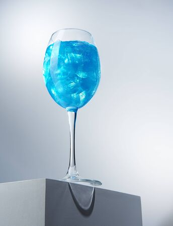 Bottom view of tasty alcohol or non-alcohol beverage in high-stemmed glass. Refreshing drink in wineglass standing on white cube. Gourmet and exquisite drinks concept