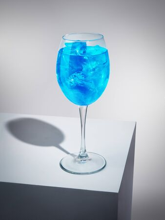 Turquoise delicious alcohol or non-alcohol drink standing on white cube. Refreshing beverage in high-stemmed wineglass. Gourmet and sophisticated drinks concept