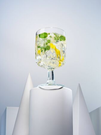 Delicious alcohol or non-alcohol cocktail in stylish crystal glass. Lemon squash with sliced lime and mint standing among geometric shapes. Gourmet and exquisite drinks concept 写真素材