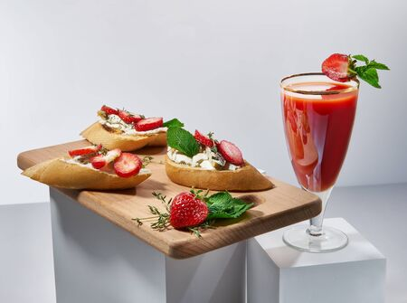 Delicious sweet red cocktail and canapes with butter and yummy strawberries. Nice beverage and snacks on white cubes. Gourmet and sophisticated drinks and appetizers concept Stock Photo