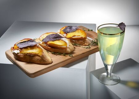 Tasty lemonade and toasts with butter, fried peach, thyme and basil. Yummy beverage and snacks on white cubes. Gourmet and sophisticated drinks and appetizers concept