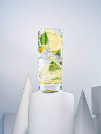 Tasty refreshing lemonade with sliced lime and fresh mint. Delicious beverage in stylish crystal glass standing among geometric shapes. Gourmet summer drinks concept 写真素材