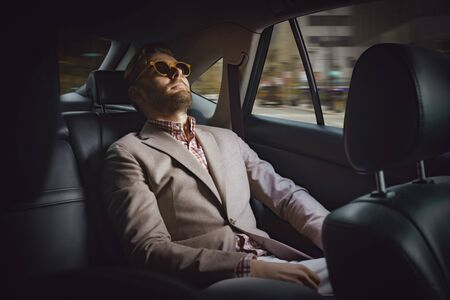Portrait of joyful businessman sitting in modern automobile and wearing fashionable suit and glasses. Successful corporation worker relaxing in expensive salon of new car. Wish came true concept 스톡 콘텐츠 - 132075403