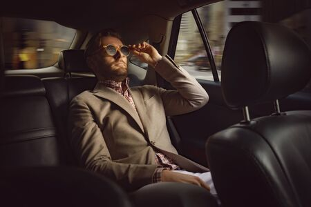 Portrait of self-confident businessman sitting in modern automobile and touching expensive black glasses with grace and gladness. Wish came true concept