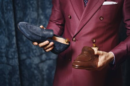 Close-up of businessman standing in modern showroom and holding fashionable footwear. Smart fashion designer presenting best type of stylish shoes. Bootmaker workshop concept