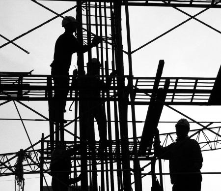 Construction Workers in Silhouette -- high up on the scaffolding Stock Photo