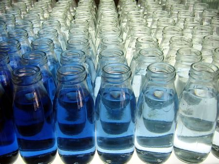 Milk Bottle Line-Up -- filled with various shades of blue liquid photo