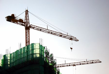 Highrise Construction -- with two cranes seen in outline and scaffolding