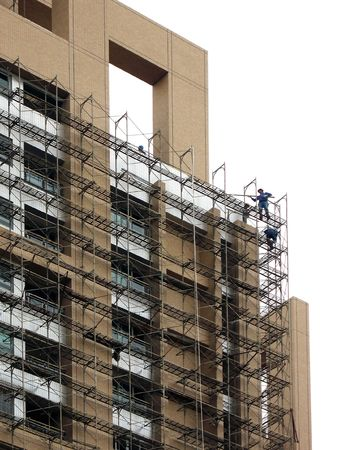 Highrise Construction -- workers are dismantling the scaffolding after building completion photo