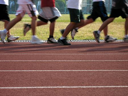 Runners in Motion -- exercising on an outdoor athletic running track Stock Photo