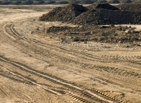 Construction Site -- with large piles of dirt and tracks from heavy equipment Stock Photo