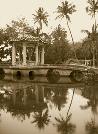 Old Chinese Garden -- with a pavilion, bridge and palm trees reflecting in the water Stock Photo - 1018421