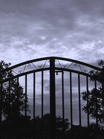 iron gate: Iron Gate -- seen against a dark and foreboding sky Stock Photo