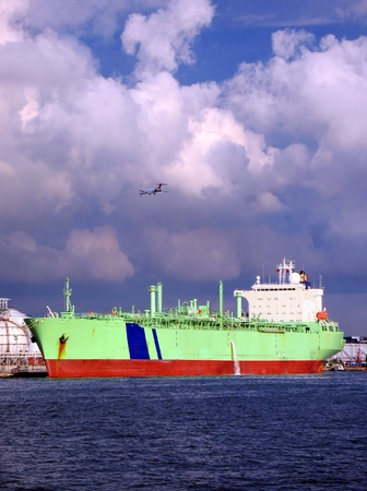Large Oiltanker -- resting in port, with an airplane overhead Stock Photo - 1677896