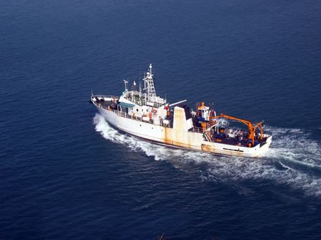Ship at Sea -- a medium sized vessel is heading out to sea Stock Photo