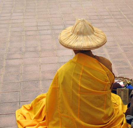 beg: Chinese Monk -- in yellow robe, begging for alms and selling trinkets