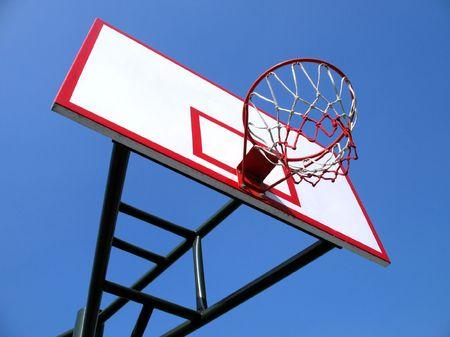 backboard: Clean basketball hoop and backboard against a blue sky Stock Photo