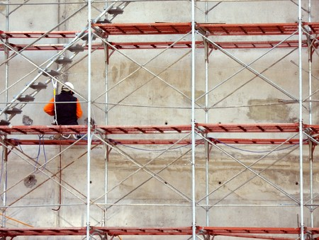 A construction worker is sitting on a metal scaffolding