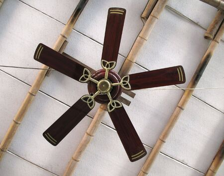 A ceiling fan with five blades on a simple bamboo ceiling