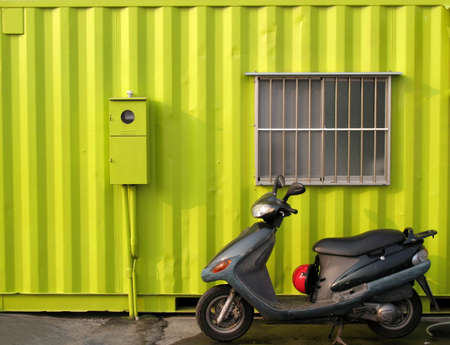 A shipping container used as a house with a scooter photo
