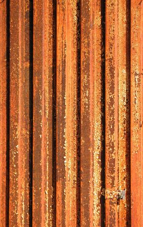 severely: A corrugated metal sheet that has been severely damaged by rust