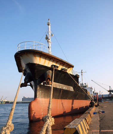 corrosion: A black freight ship is tied up in port