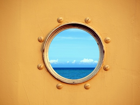Looking through a porthole of a ship one can see the blue ocean and sky. Stock Photo