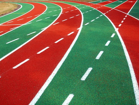 A running track in a stadium with markings in white, red and green and solid and broken lines