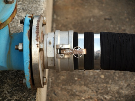 A thick fuel hose is connected to a blue steel pipeline