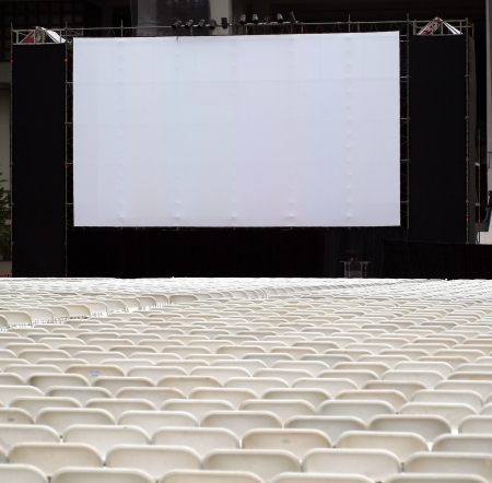 projection: Rows of white plastic chairs are set up for an outdoor movie show