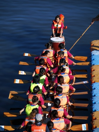 KAOHSIUNG, TAIWAN - JUNE 6: A team of female rowers waits at the starting line for the dragon boat race on the Love River on June 6, 2011 in Kaohsiung