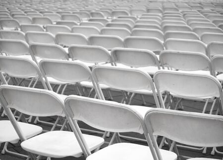 folding chair: Rows of plastic chairs are set up for an outdoor  performance Stock Photo